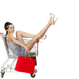 Young beautiful brunette girl sits in an empty shopping cart wit Royalty Free Stock Photos