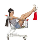 Young beautiful brunette girl sits in an empty shopping cart wit Stock Image