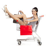 Young beautiful brunette girl sits in an empty shopping cart wit Royalty Free Stock Image