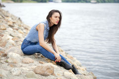 Young beautiful brunette girl sitting on the rocks on the river Royalty Free Stock Image