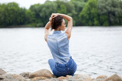 Young beautiful brunette girl sitting on the rocks on the river Stock Image