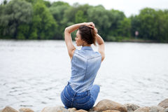 Young beautiful brunette girl sitting on the rocks on the river Stock Images