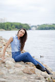 Young beautiful brunette girl sitting on the rocks on the river Royalty Free Stock Photography