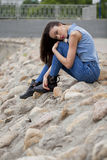 Young beautiful brunette girl sitting on the rocks on the river Stock Photo