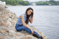Young beautiful brunette girl sitting on the rocks on the river Stock Photos