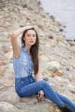Young beautiful brunette girl sitting on the rocks on the river Royalty Free Stock Photo