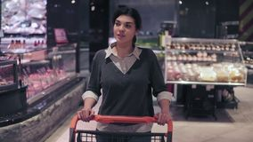 Young beautiful brunette girl smiles enjoying walking in grocery store with push cart. Shopping in a supermarket