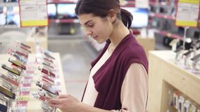 Young beautiful brunette girl smiling while picking a phone in a electronics store. Checking out apps in smartphone. Young beautiful brunette girl smiling while stock video