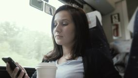 Young Beautiful Brunette Girl Travelling By Train, Looking Out The Window And Using Her Smartphone, Travelling Concept. 4K stock footage
