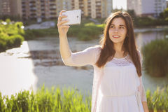 Young beautiful brunette girl in white dress photographing herse Royalty Free Stock Photo