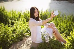 Young beautiful brunette girl in white dress photographing herse royalty free stock photos