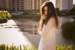 Young beautiful brunette girl in white dress standing near river Royalty Free Stock Photos