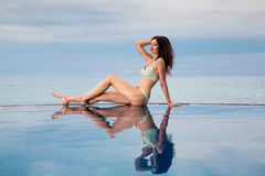 Young beautiful brunette girl in a white swimsuit is next to the Royalty Free Stock Images