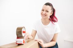 Young beautiful brunette girl in a white t-shirt packs cardboard boxes with a dispenser and adhesive scotch adhesive royalty free stock images