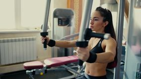Young beautiful brunette girl wih long hair makes a butterfly exercise at the fitness centre. 4 k