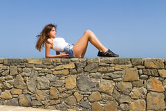 Young beautiful brunette in jean shorts enjoys the Stock Photo