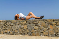 Young beautiful brunette in jean shorts enjoys Royalty Free Stock Photos