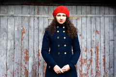 Young beautiful brunette in a knit beret and a coat Stock Photos