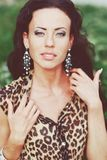 Young beautiful brunette in a leopard dress outside Stock Photo