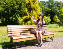 Young Beautiful Brunette Makes Selfie Sitting On A Bench Stock Photo