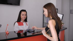 Young beautiful brunette, paying by credit card. Cosmetology Clinic. stock video