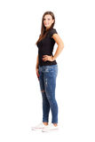 Young beautiful brunette posing with arms on her hips. Stock Photography