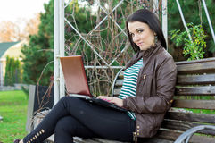 Young beautiful brunette student in profile sits Stock Images