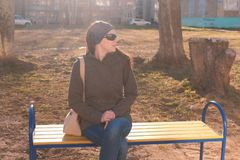 Young beautiful brunette in sunglasses looks around and waited for someone sitting on the bench in city yard of multi royalty free stock photography