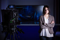Young beautiful brunette television announcer at studio during live broadcasting.Female TV director at editor in studio. royalty free stock images