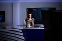 Young beautiful brunette television announcer at studio during live broadcasting.Female TV director at editor in studio. stock image