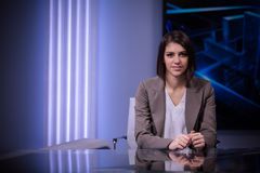 Young beautiful brunette television announcer at studio during live broadcasting.Female TV director at editor in studio. Recording at TV studio with television royalty free stock images