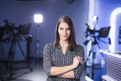 Young beautiful brunette television announcer at studio standing next to the camera. TV director at editor in studio. Recording at TV studio with television royalty free stock photography
