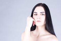 Young, beautiful brunette touching her cheek by hand and looking at the camera Stock Photography