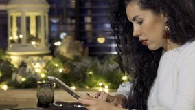 Young beautiful brunette uses digital tablet in cafe. Young beautiful brunette sits in cafe next to the table and uses digital tablet. Pretty woman searches stock video
