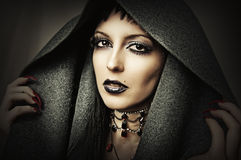 Young beautiful brunette woman. In gray hood with fashion gothic make up and ancient necklace Stock Photos