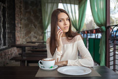 Young beautiful brunette woman answering a phone call in cafe terrace with a cappuccino cup Stock Photos