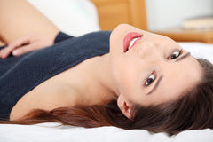 Young and beautiful brunette woman on bed Royalty Free Stock Image