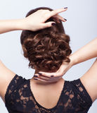 Young beautiful brunette woman in black dress from back side Stock Photos