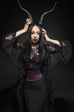 Young beautiful brunette woman in black fantasy costume Stock Photography