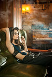 Young beautiful brunette woman in black male  trousers, hat and braces relaxing on a sofa in vintage scenery. Romantic mysterious Stock Photography