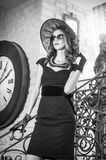 Young beautiful brunette woman in black standing on stairs near an over sized wall clock. Elegant romantic mysterious lady Royalty Free Stock Photo