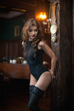 Young beautiful brunette woman in black tight fit corset posing sensual in vintage scenery. Romantic mysterious young lady. With long legs in luxurious interior Royalty Free Stock Photography