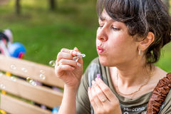 Young beautiful brunette woman blowing soap bubbles outdoor Stock Photos
