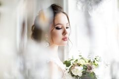 Beautiful brunette woman with bouquet posing in a wedding dress. Young beautiful brunette woman with bouquet posing in a wedding dress Stock Photo