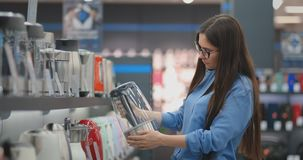 Young beautiful brunette woman chooses an electric kettle to buy. Holds a device in his hands, studies the price tags. And the characteristics and design of the stock video