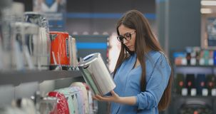 Young beautiful brunette woman chooses an electric kettle to buy. Inspects the device, examines the price tags and the. Characteristics of the model stock footage