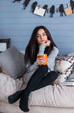 Young beautiful brunette woman with cup of coffee sitting home on the sofa by the window. Royalty Free Stock Photo