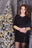 Young beautiful brunette woman in the dark dress on christmas, w Royalty Free Stock Photos