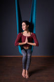 Young beautiful brunette woman doing fly yoga. Sitting in hammoc Stock Images