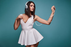 Young beautiful brunette woman in dress with headphones Royalty Free Stock Photos
